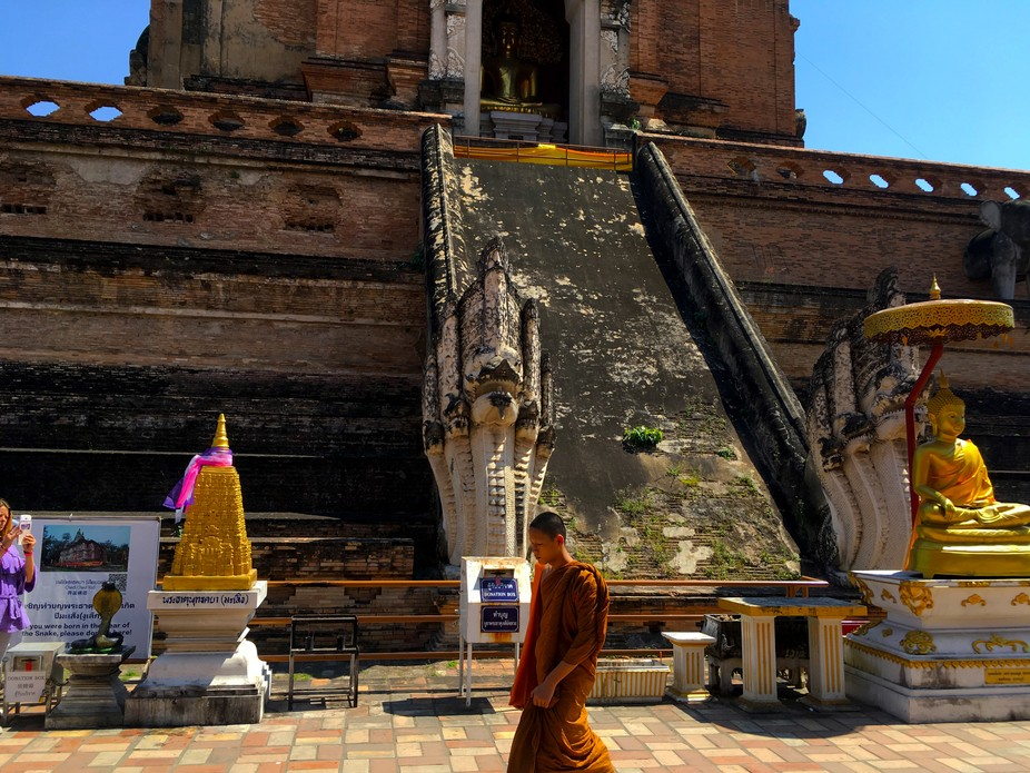 Buddhist monk taking a stroll in Chang Mai Thailand. A very old ruins in the background that was mostly destroyed in an earthquake supposedly a 1000 years ago?