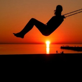 This photo was taken on a beach in Manistee, Michigan. This girl was swinging and shot directly above the setting sun.