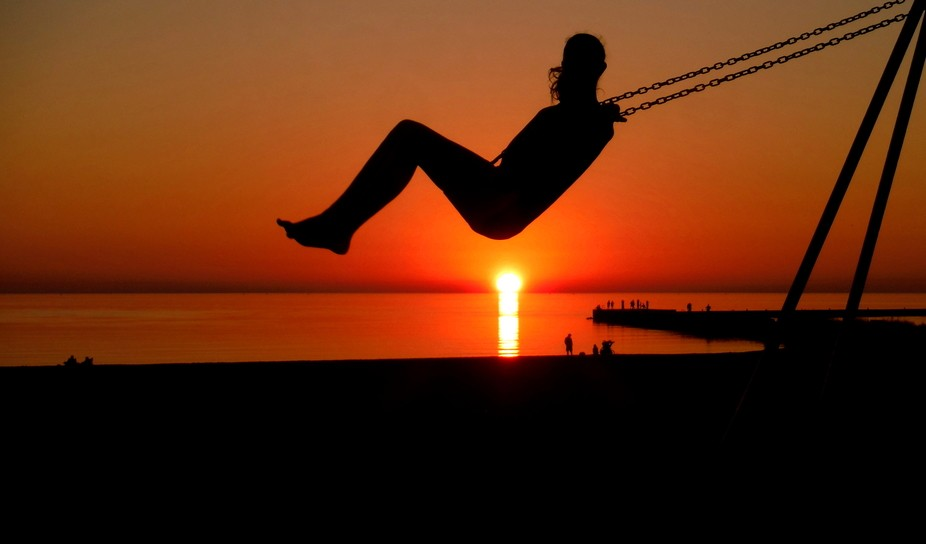 This photo was taken on a beach in Manistee, Michigan. This girl was swinging and shot directly a...