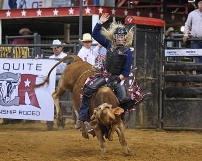 Cowboy girl riding a bull