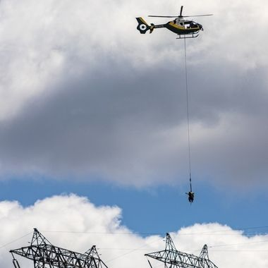 Two power linemen being sling loaded by helicopter  to the next tower near Banning, California