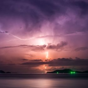 Taken from a Thai beach during a particularly beautiful light show across the bay.