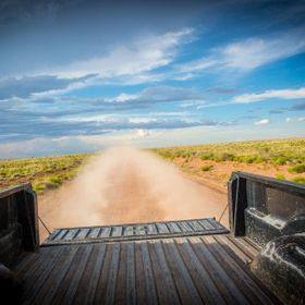 The view out the back of the pickup truck as it races down a lonley dusty road in Northern Arizona.