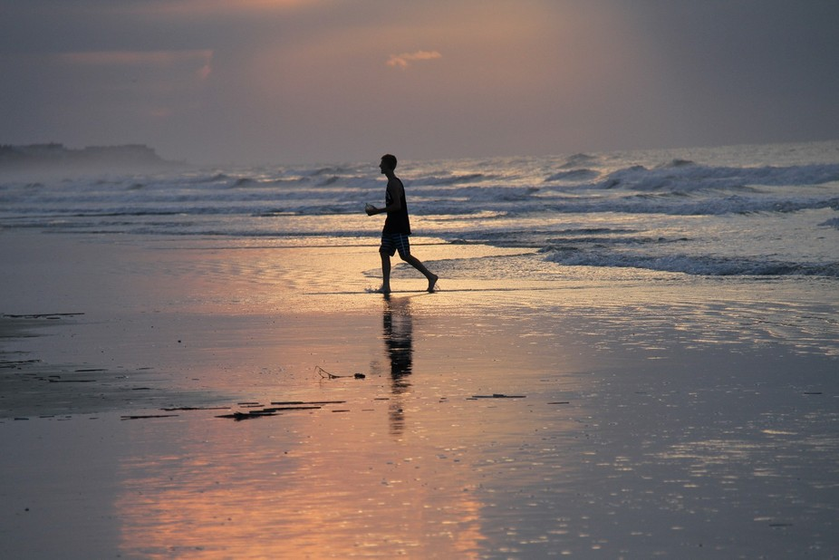 this is a young man on a South Carolina beach with a beautiful sunrise as a backdrop