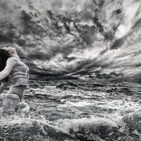 Composite image in Black and White depicting woman with head into the wind an storm.
