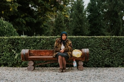 A gypsy quietly sits outside the Cathedral of Curtea de Argeș, Romania.
