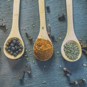 A selection of mixed herbs and spices on spoons.