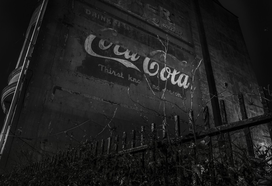 Old fading Coke ad on side of Glasgow tenement.
