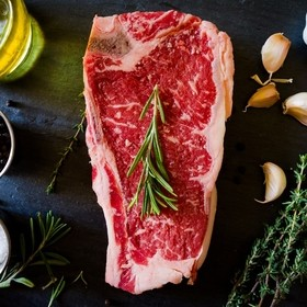New York Strip Steak Bone In fresh cut from the local butcher shop. raw meat