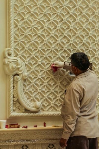 Workman sanding individual plaster designs
