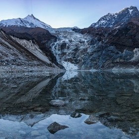 Tranquil waters of Birendra lake reflecting Manaslu mountain shortly before sunset. The lake is fed by Manaslu glacier and is situated near Samag...