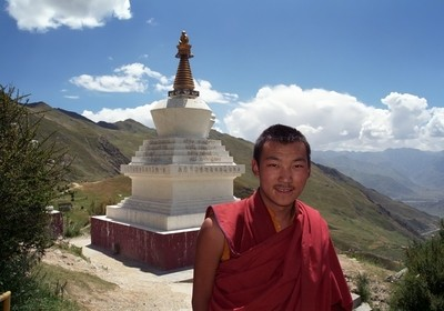 Tibetan monk of Buddhist monastery Druk Yerpa near the ritual construction Stupa.