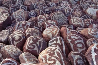 "Pebbles from sacred Lake Manasarovar with hieroglyphs and main  Buddhist mantra ""Om Mani Padme Hum""."