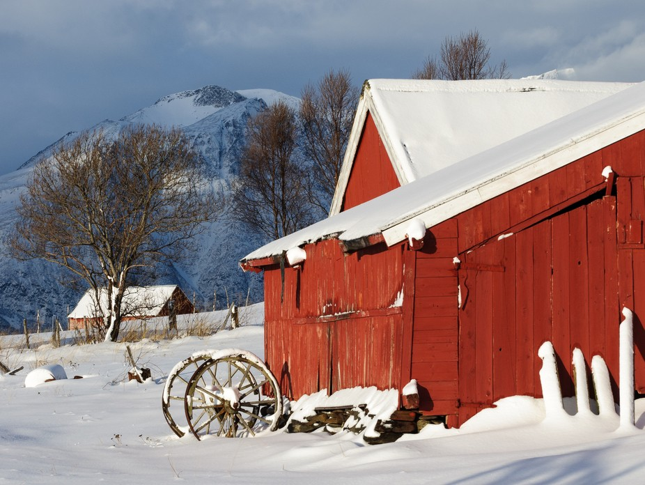 The sun came out of the cloud for a few moments to light this classic red Norwegian barn on the foreshore with the Lyngen Alps behind.  This fresh snow had been falling all the previous day. These wheels outside the barn add an air of mystery.