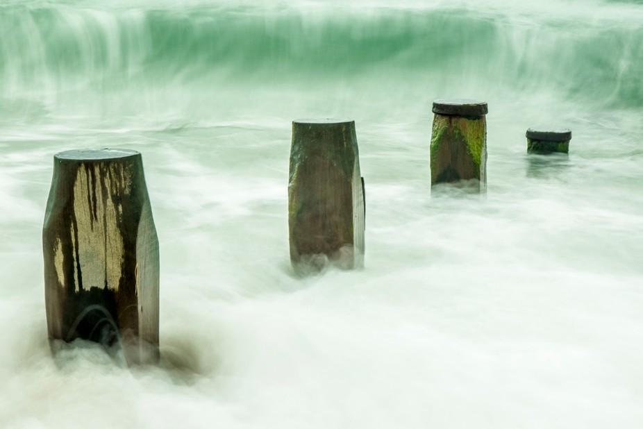 Hayling Island, South Coast, UK. Long Exposure of crashing waves against wooden beach defences.