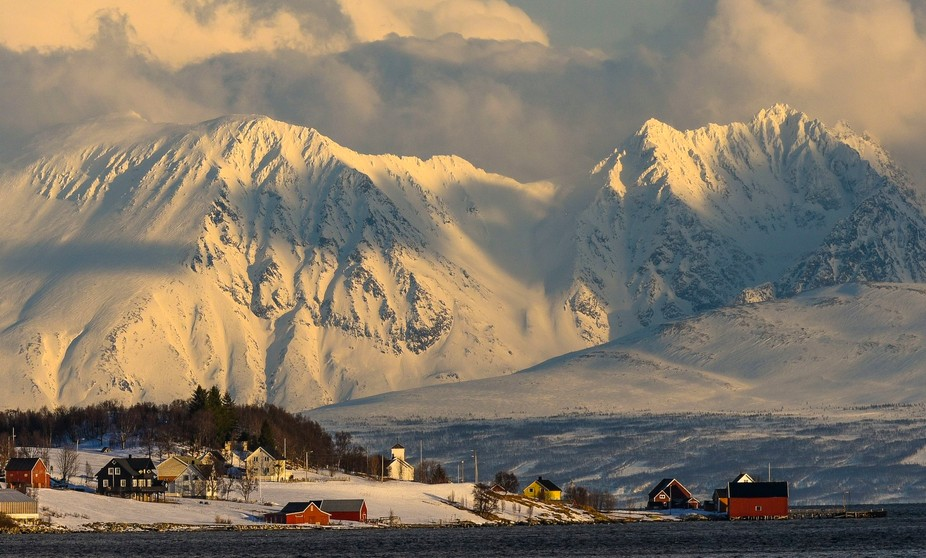 This little hamlet is dwarfed by the snow covered mountains on the other side of the Fjord.  We left Oslo in the morning and took this picture on a late February afternoon to the north of Tromsø