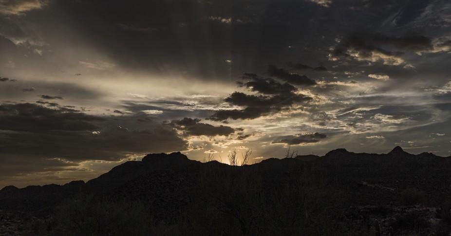 Subtle rays of sunlight streak the sky at sunset behind a mountain range