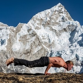 Performing Mayurasana or Peacock pose in front of Nuptse and Everest mountains. Kala Pattar viewpoint, Himalayas, Nepal.