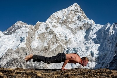 Performing Mayurasana or Peacock pose in front of Nuptse and Everest