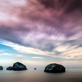 Dramatic purple sky over some rocks in the ocean