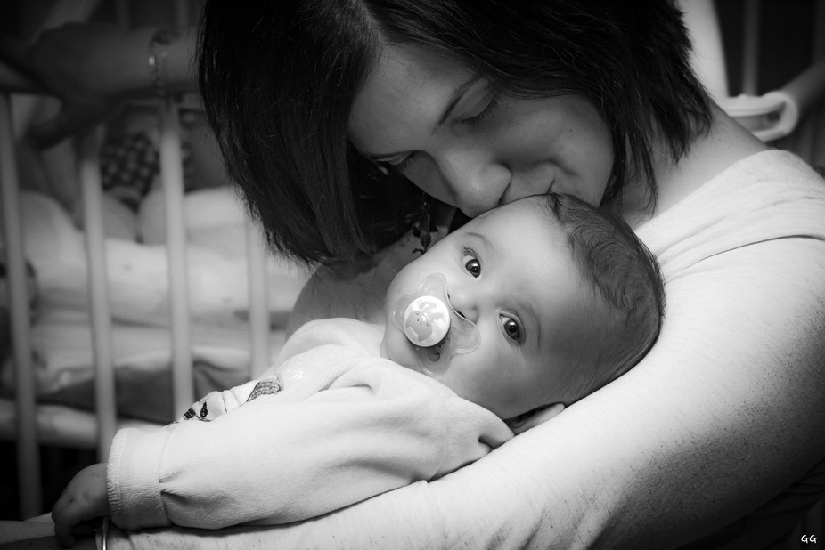 A baby facing the camera, with her mother taking care of her