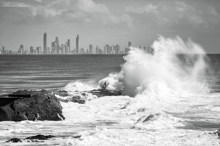 A beautiful wave smashes over the surfer while the city watches in the background