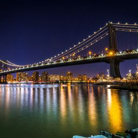The Manhattan Bridge glows during the evening hours as the stars shine above. Shot from Brooklyn Bridge Park, New York City.