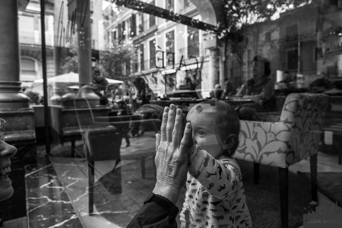 this situation I have seen in Palma de Mallorca.The child inside was looking to the grandma outside and both played with their hands.