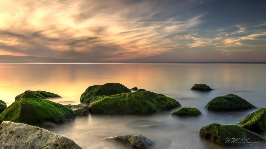 Long exposure of sunset with green rocks
