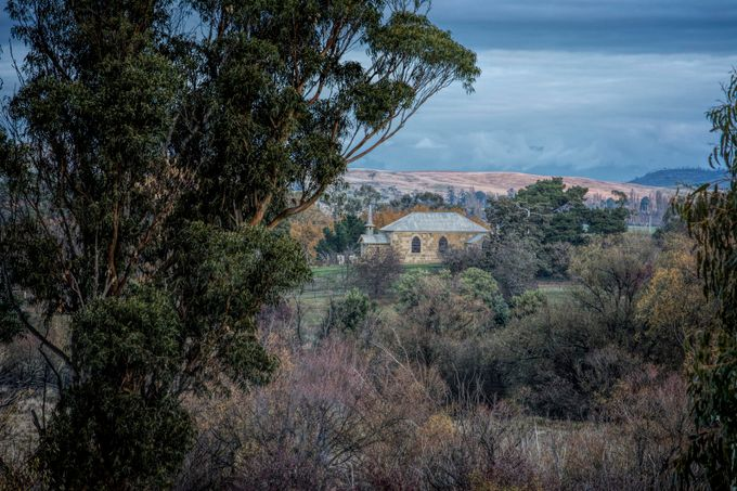 Perched on a small knoll above the Ouse River and township is the church,St Johns the Baptist, and its collection of early settlers graves. Tasmania.