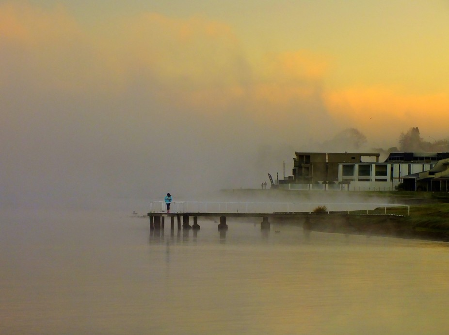 The sunrise paints the morning fog at Lake Taupo in the North Island of New Zealand.