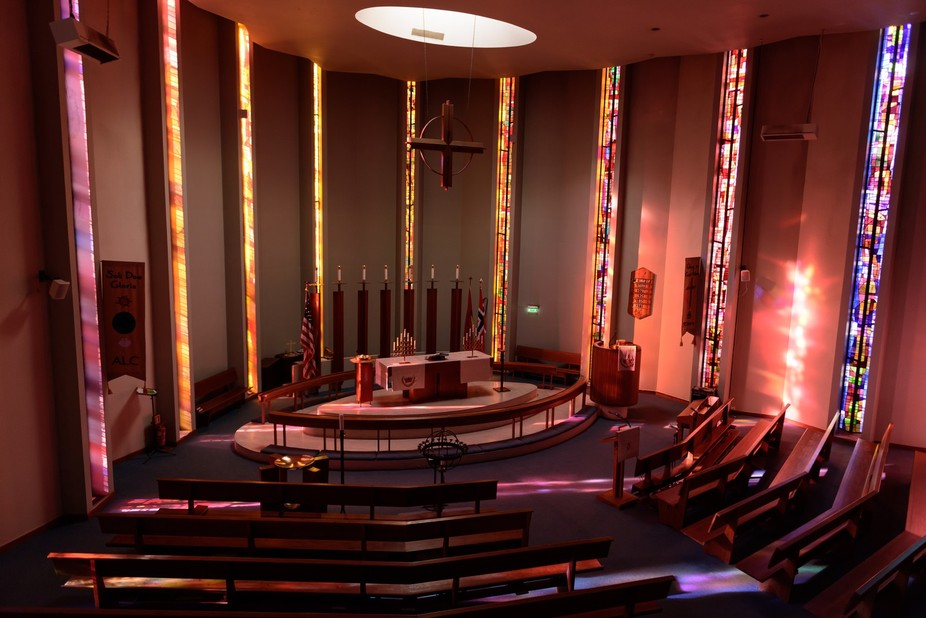 This is the American Lutheran church in Oslo Norway. It was built using funds raised by Norwegian immigrants to the USA about 52 years ago.   Late in the evening in April the sun streams in through the stained glass windows producing this beautiful lighting.  This was taken from the choir loft