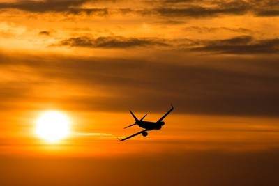 A plane flying towards a beautiful sunset