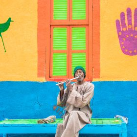 Egyptian Nubian is playing a piece of music on the banks of the Nile River by using the flute