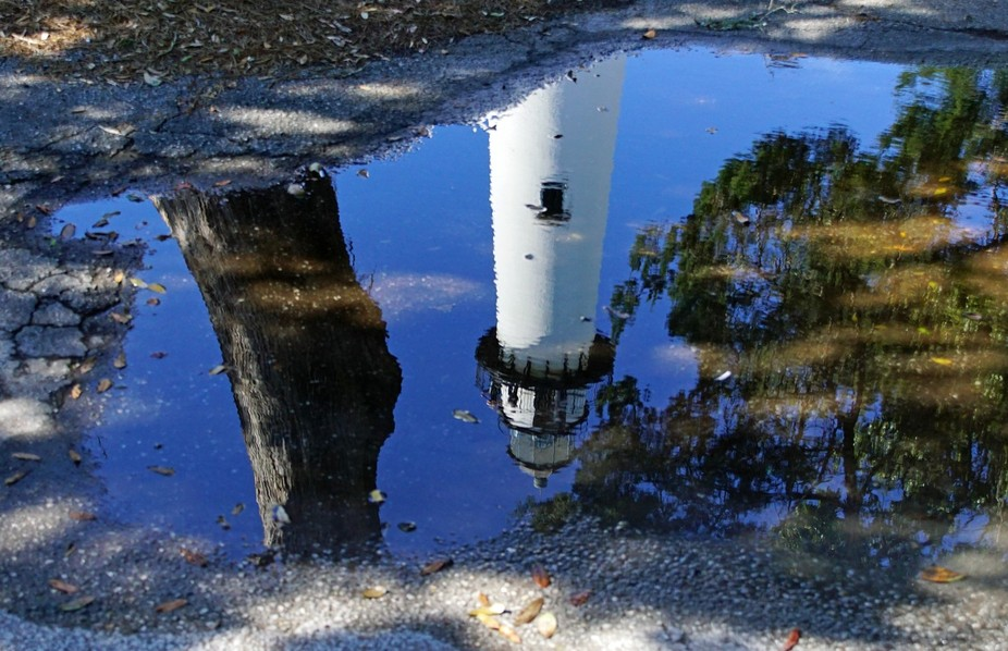 Big lighthouse, small puddle, blue sky kind of day.