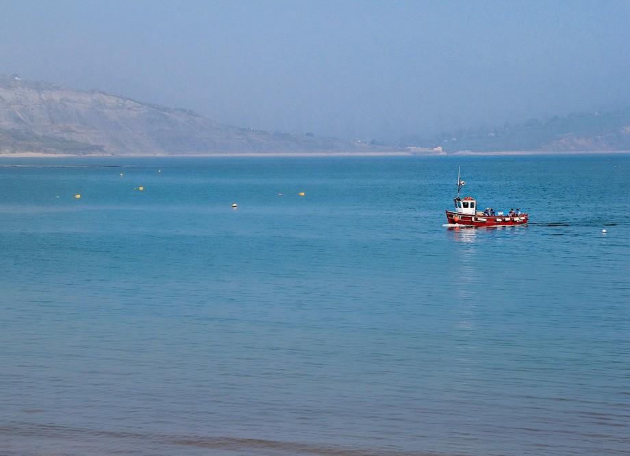 Fishing boat on the water in Lyme Regis, Dorset, UK.
