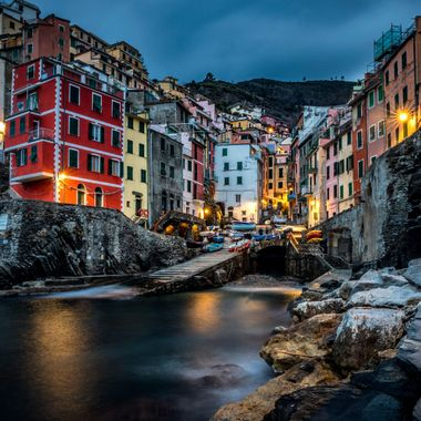 The village of Riomaggiore sits dramatically on the Gulf of Genoa at the upper edge of Italy's boot.  It is a photographer's dream setting.  The city offers up close access to amazing colorful buildings perched majestically on the water's edge.