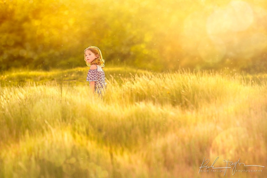 A little girl standing in grasslands during the best part of the day... golden hour!