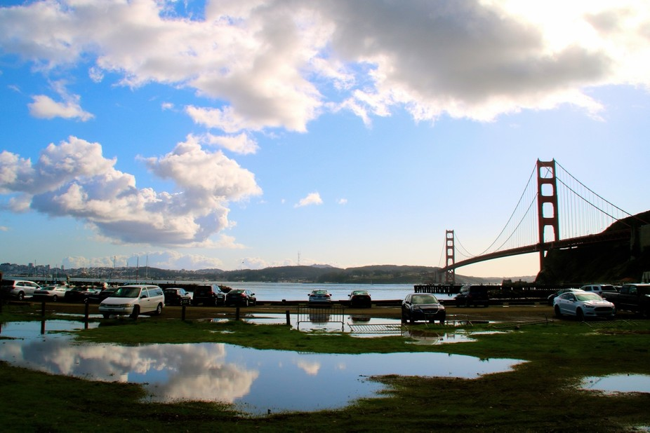 Puddle stationed near the golden gate bridge reflecting the cloudy sky.