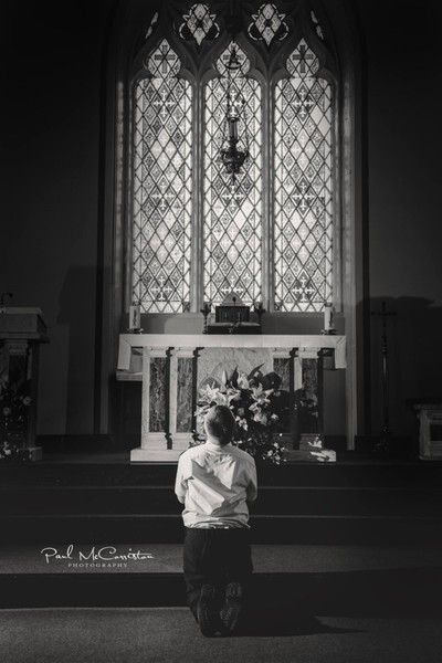 1st Holy Communion. Low key shot of the child praying at the alter below the amazing stained glass window.