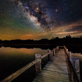 A small pier in lake cuyamaca with a view of the milky way in front of it