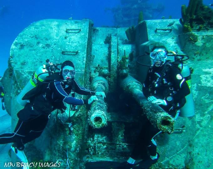 My 2 dive buddies posing on the main guns of the Tippets. Cayman Brac