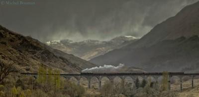 Steam-train passing Glenfinnan Railway-bridge Scotland .