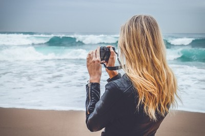 Woman photographing the ocean
