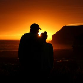 Lovers enjoy the view of the sunset at Curio Bay, NZ.