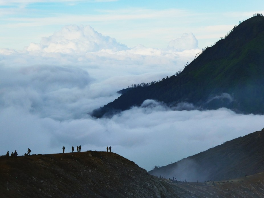 Grand view above the cloud at the peak of Mount Ijen, Indonesia. The tiny people in contrast to t...