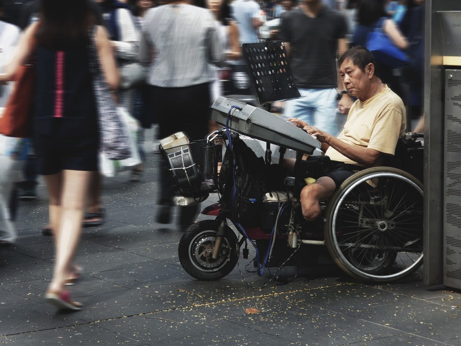Disabled street musician making a living on Orchard Road, Singapore. The  blur of the surrounding...