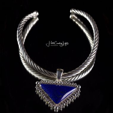 "Sometimes you just don't have a lot of time to execute a shot you need to complete for the client right on the spot.  After shooting a set of fine art reproductions for a gallery owner, the client handed me this beautiful heavy silver rope necklace cuff with a Lapis stone and asked if we could shoot this.  We were out of time, and I wanted the challenge.  I found a small mirror mounted on a swivel, placed the necklace on the surface, and leveled it with a book.  Shooting from above on a 7' tripod and Arca ball-head, with a 55mm Nikkor Micro F/3.5, the focus point was the tip of the blue stone triangle, and rolling off toward the back.  Two speed lights in soft boxes mounted to either side, the one on the right closer in, to create that highlight and emphasize the mass of that stone. To manage the ceiling reflection, I held a 5'x7' pop=open cloth shroud directly over the set.  One test and one final exposure is all it took, got exactly the look I wanted - polished black surface, double reflection to show the size and depth of the necklace, and strong detail upfront.   It's not the worlds most important or best shot, but for me it's a ""Merit Badge"" -- I was able to produce this image in less than 3 minutes, live, under deadline."