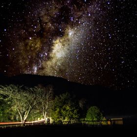 A composite photo from 6 shots taken at the Blue Lake, Rotorua, NZ.  The first five recorded the sky and the 6th recorded light from a car that c...