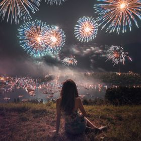 A girl watching an amazing fireworks show on Lake Como.